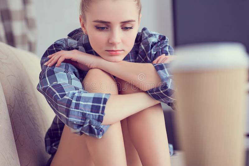 在家不快乐的孤独的沮丧的十几岁的女孩,她坐在长沙发和用他的脚扶植她的头 图库摄影