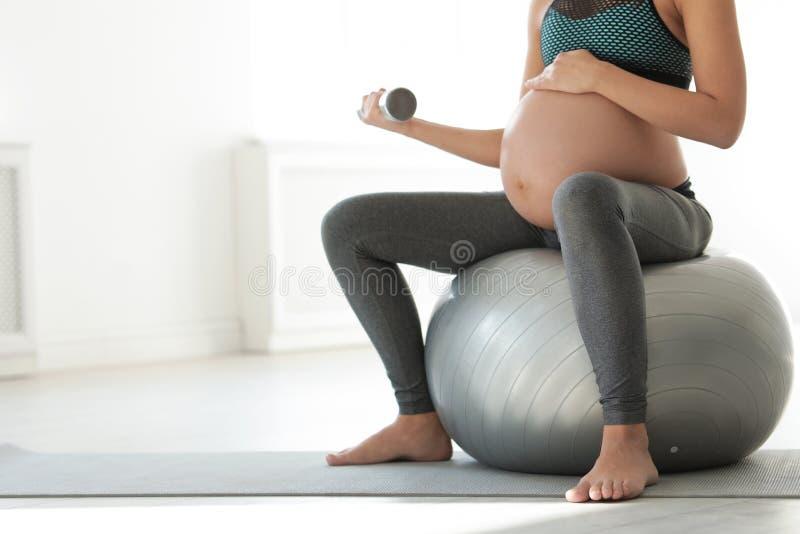 在家举哑铃的健身衣裳的年轻孕妇,特写镜头 库存图片