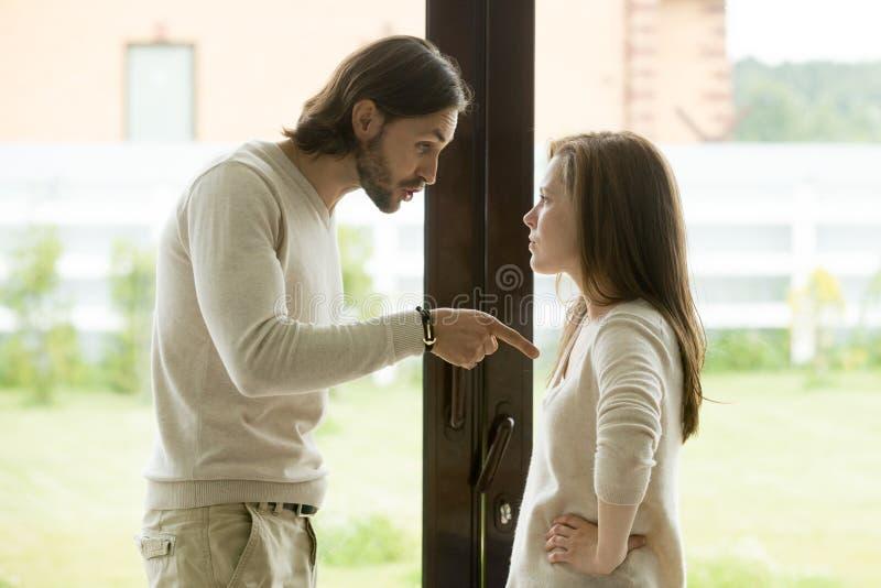 在家争论年轻的夫妇,指向手指的人责备妇女 库存照片