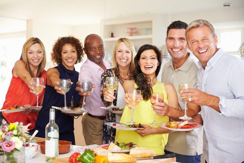 在家享受晚餐会的成熟朋友画象  图库摄影