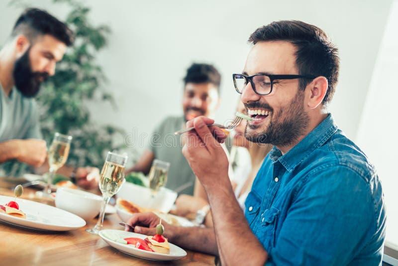 在家享受晚餐的小组愉快的年轻朋友 库存照片
