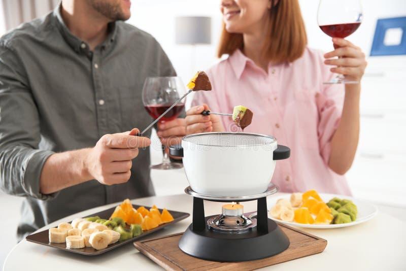 在家享受涮制菜肴晚餐的愉快的夫妇 免版税库存图片