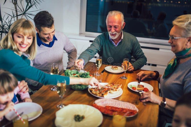 在家享受膳食的家庭在桌附近 免版税库存图片