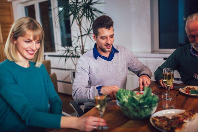 在家享受膳食的家庭在桌附近 免版税库存照片