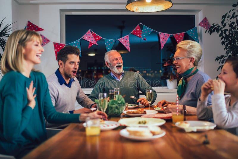 在家享受膳食的家庭在桌附近 免版税图库摄影