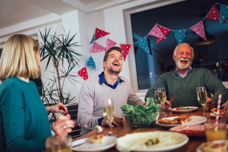 在家享受膳食的家庭在桌附近 库存照片