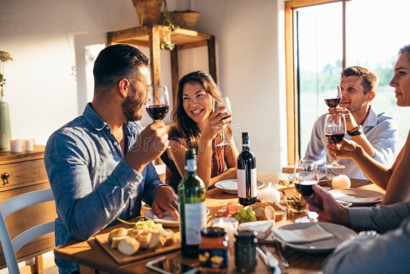 在家享受膳食的小组朋友一起 免版税库存图片