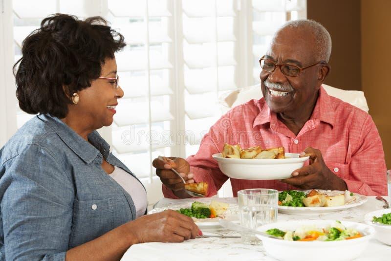在家享受膳食的高级夫妇 免版税库存照片