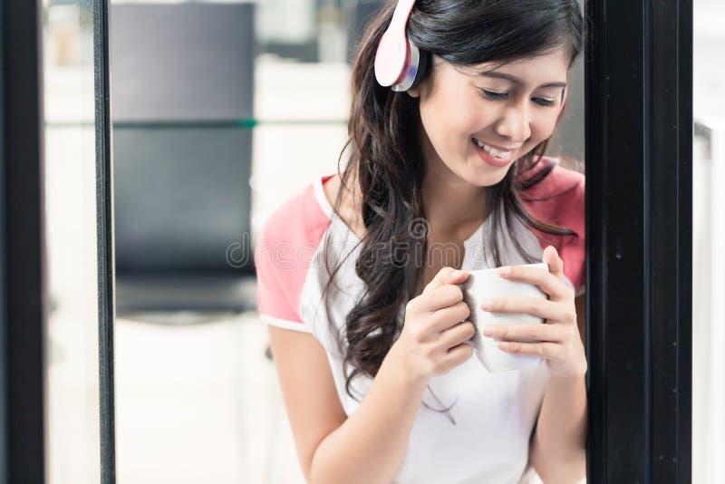 在家享受音乐用咖啡的印度尼西亚妇女 图库摄影