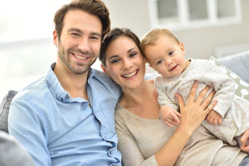 在家享用愉快的年轻的家庭画象  免版税库存照片