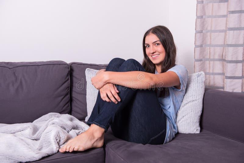 在家休息与她的膝盖的年轻可爱的妇女画在t 库存图片