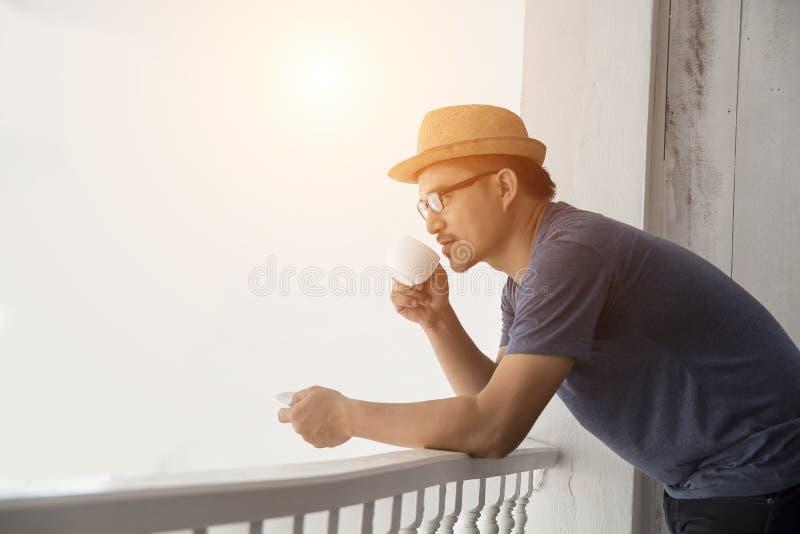 在家休息有日出的年轻行家人阳台 免版税图库摄影