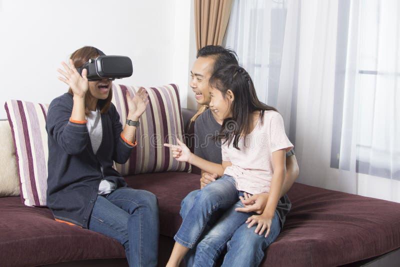 在家佩带虚拟现实风镜的愉快的亚洲家庭 免版税库存照片