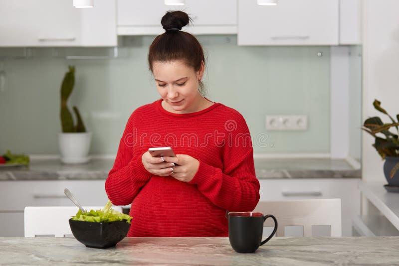 在家使健康孕妇惊奇的图象在厨房里使用检查的人脉或电子邮件手机,吃沙拉 免版税库存图片