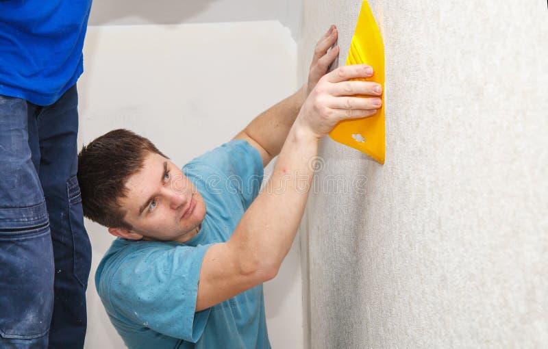在家使墙纸光滑的年轻工人 图库摄影