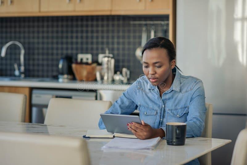 在家使用一种数字片剂的年轻非裔美国人的妇女 免版税图库摄影
