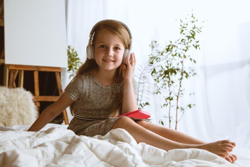 在家使用不同的小配件的女孩 免版税库存图片