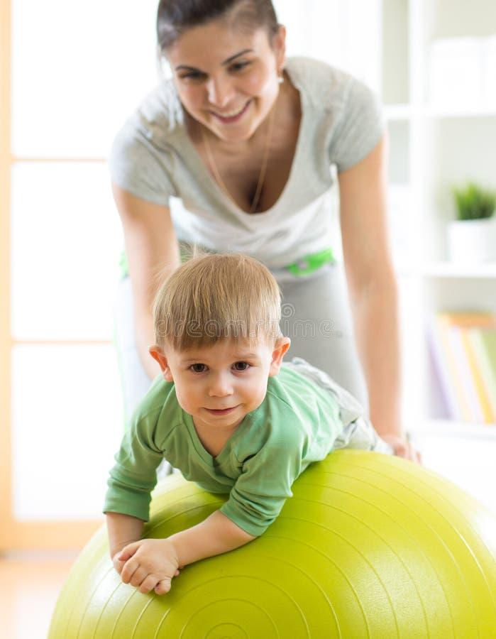 在家使用与与母亲的体操球的婴孩 免版税库存照片