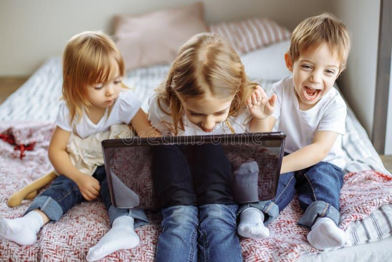 在家使用与便携式计算机的孩子 库存照片