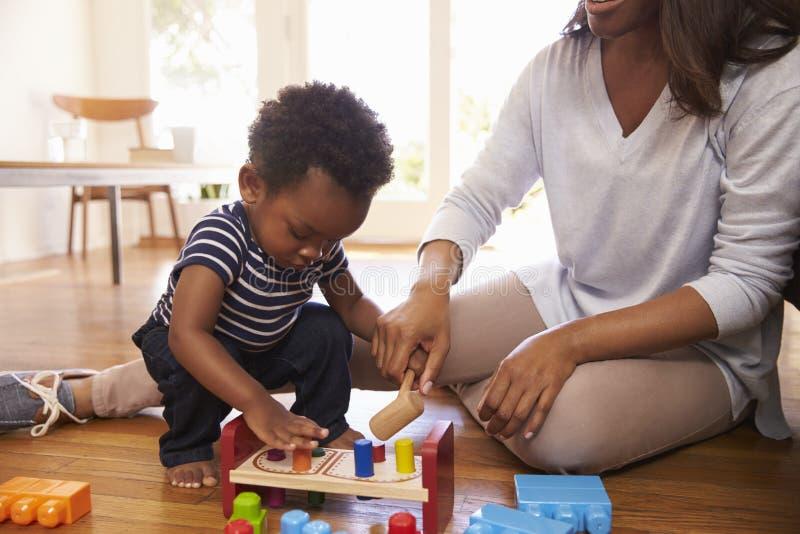 在家使用与在地板上的玩具的母亲和儿子 免版税库存照片