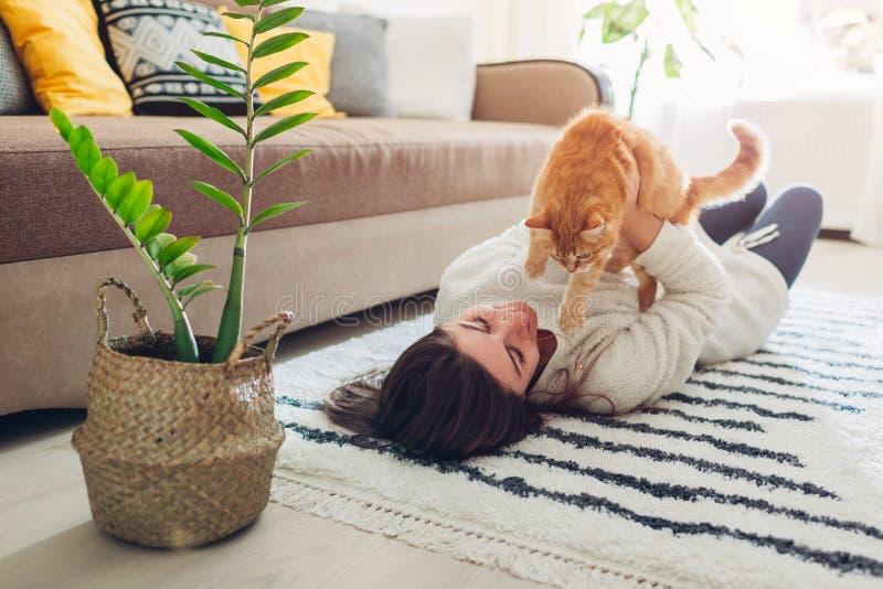 在家使用与在地毯的猫的年轻女人 主要说谎在与她的宠物的地板上 免版税图库摄影