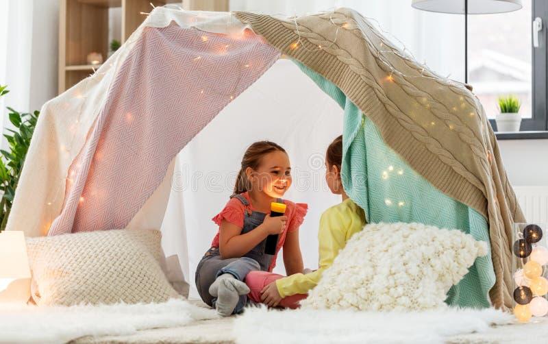 在家使用与在孩子帐篷的火炬的女孩 免版税库存照片