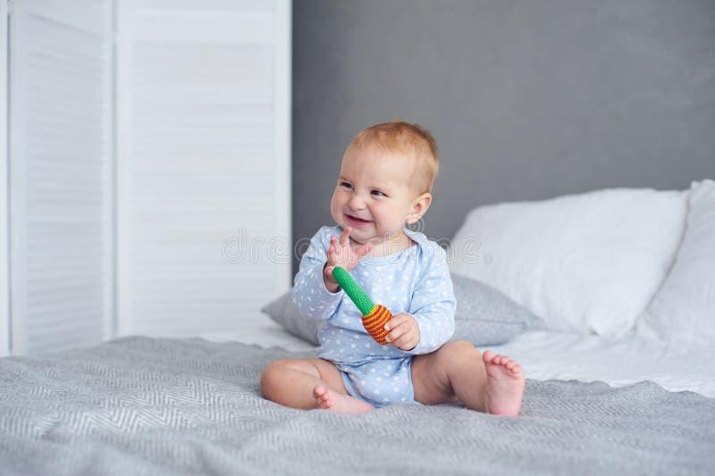 在家使用与在床上的被编织的玩具的逗人喜爱的男婴 库存图片