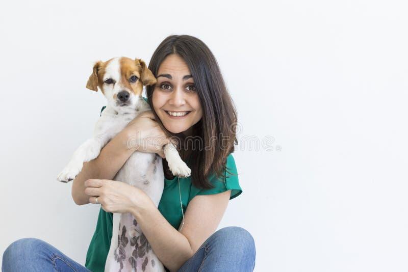 在家使用与她小的逗人喜爱的狗的美丽的年轻女人 生活方式画象 对动物概念的爱 奶油被装载的饼干 免版税图库摄影