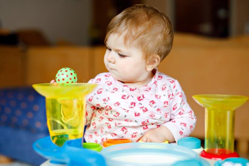 在家使用与教育玩具或托儿所的可爱的逗人喜爱的美丽的矮小的女婴 有愉快的健康的孩子 免版税库存图片