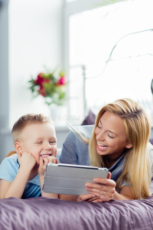 在家使用与数字式片剂的母亲和儿子 免版税库存照片