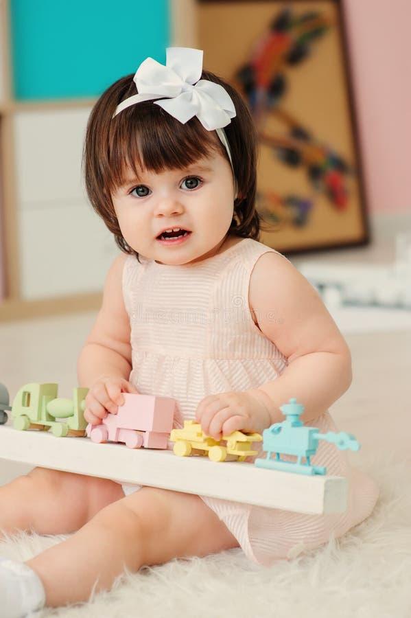 在家使用与木玩具的逗人喜爱的愉快的1岁女婴 免版税图库摄影