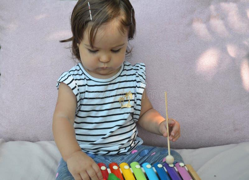 在家使用与木琴的逗人喜爱的儿童女婴小孩 创造性和教育概念 音乐的早期的stert 库存照片