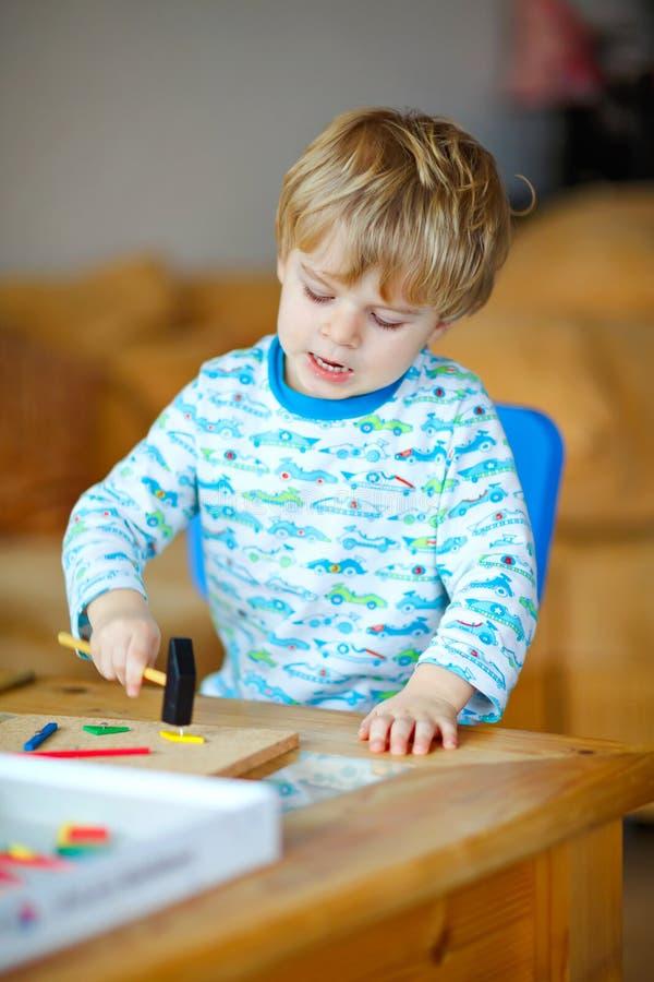 在家使用与木锤子工具的逗人喜爱的小孩男孩在车间 孩子作为杂物工的男孩戏剧 睡衣的孩子 图库摄影