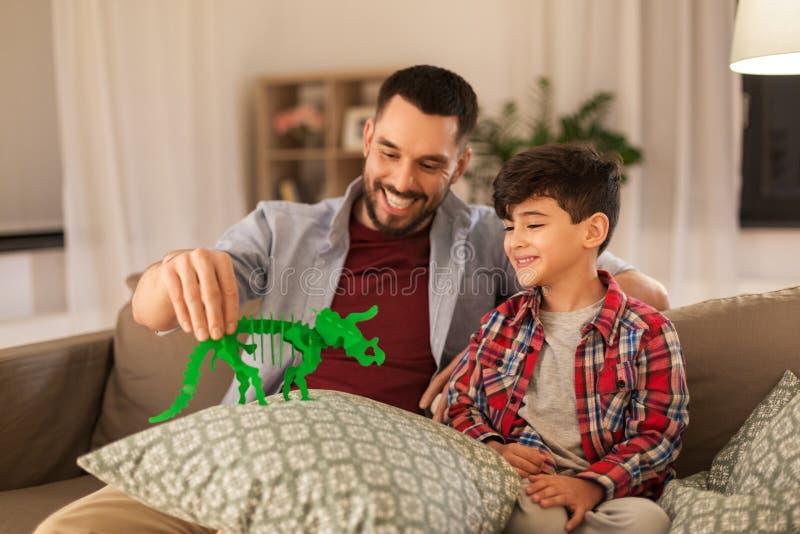 在家使用与玩具恐龙的父亲和儿子 库存图片