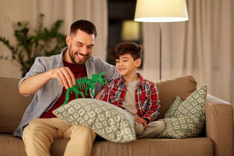 在家使用与玩具恐龙的父亲和儿子 图库摄影