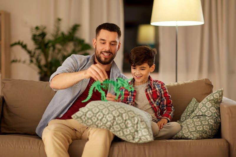 在家使用与玩具恐龙的父亲和儿子 免版税库存照片