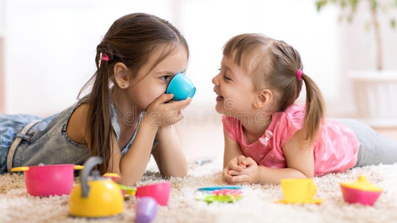 在家使用与玩具的逗人喜爱的滑稽的孩子 免版税库存图片