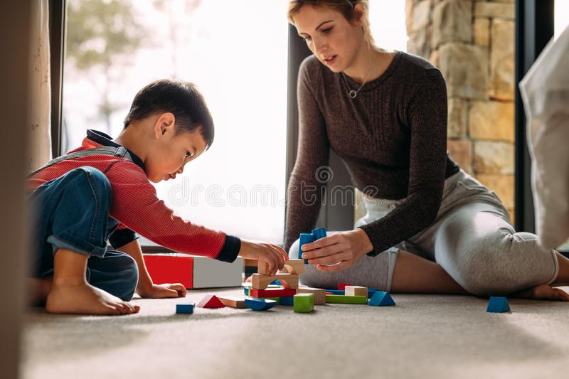在家使用与积木的母亲和儿子 库存照片