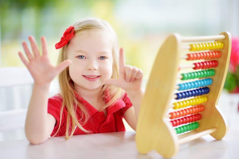 在家使用与算盘的逗人喜爱的小女孩 学会聪明的孩子计数 免版税图库摄影