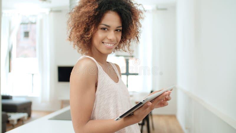 在家使用个人计算机片剂的年轻美国黑人的妇女 免版税库存图片