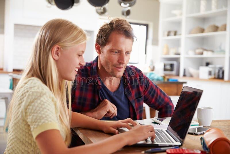 在家使用便携式计算机的父亲和女儿 免版税库存照片