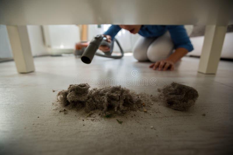在家使用吸尘器的主妇为尘土 免版税库存图片