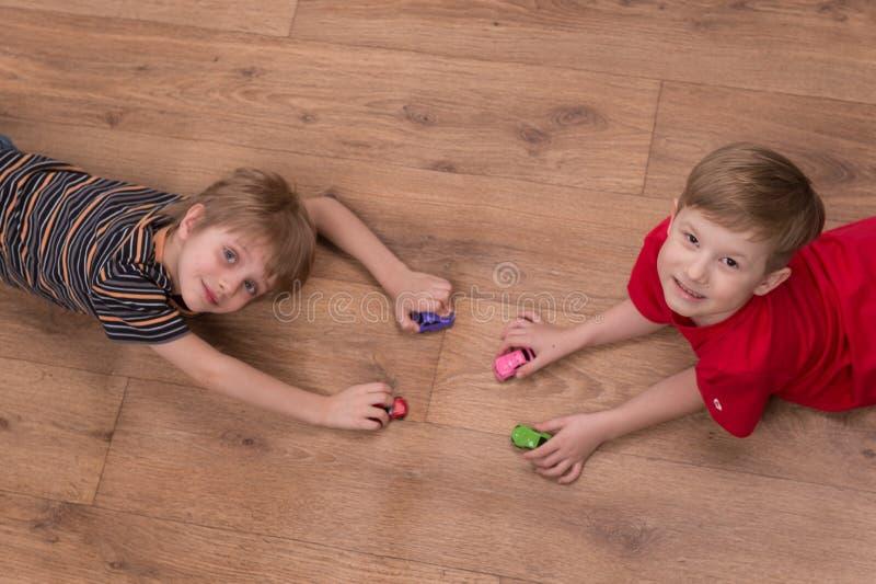 在家使用在地板上的两个朋友 免版税图库摄影