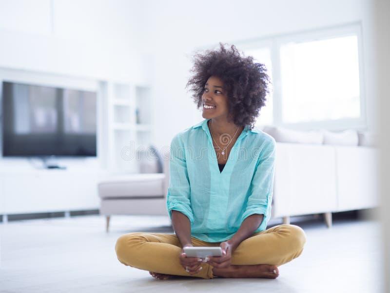 在家使用在地板上的黑人妇女片剂计算机 免版税库存图片