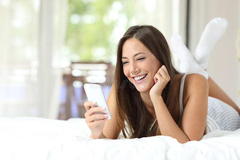 在家使用在床上的女孩一个手机 库存照片