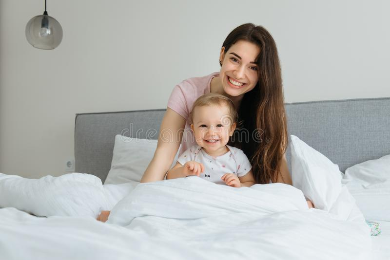 在家使用在床上的母亲和小孩女儿 免版税库存图片