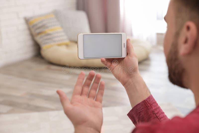 在家使用在智能手机的年轻人视频聊天 免版税库存图片