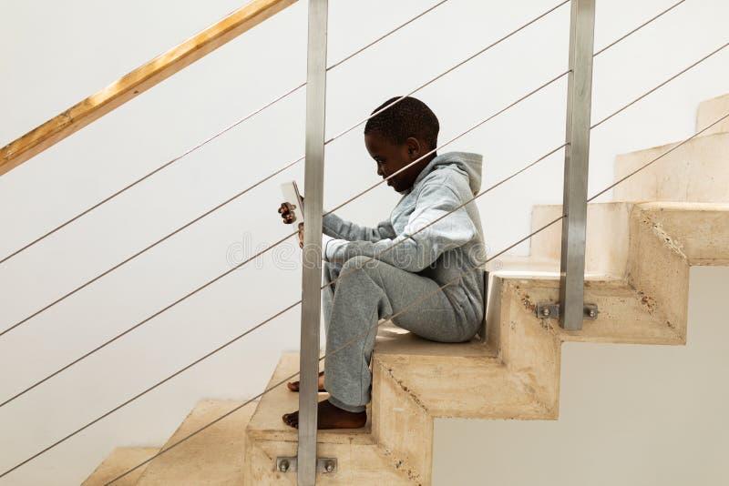 在家使用在楼梯的男孩数字片剂 库存图片