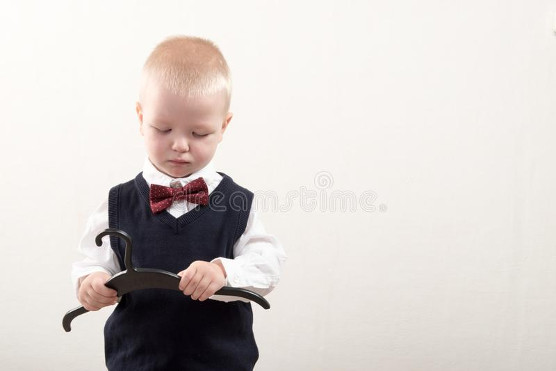 在家使用愉快的男孩 巧妙的衣裳和一个挂衣架在手上 库存照片