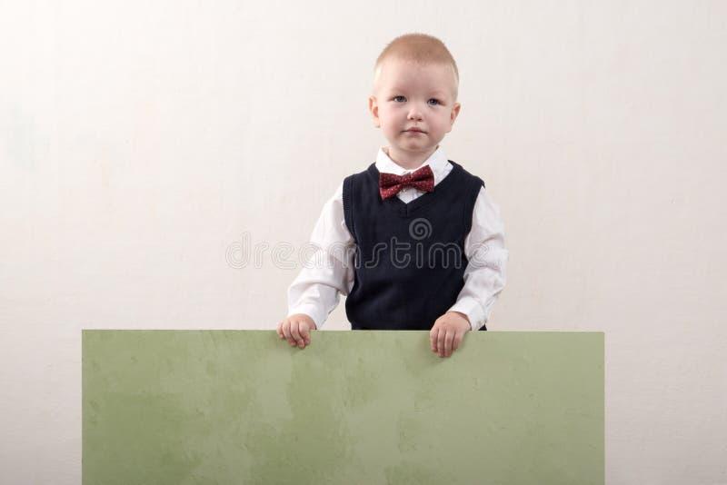 在家使用愉快的男孩 巧妙的衣裳和一个挂衣架在手上 免版税图库摄影